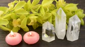 Three quartz crystals and two pink candles in front of orchid flowers