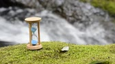 işler : Hourglass on the green moss in front of brook