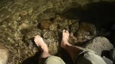 Put man of both feet in shimmering brook for cooling