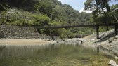Thin gentle river flowing under bridge in front of green forest in Kumamoto
