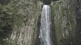 White waterfall falling over columnar joint cliff in Kumamoto
