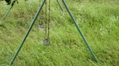 Green steel prop swing in the bright green grassy place Archivo de Video