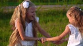 два человека : children play and laugh running around the field in summer Стоковые видеозаписи