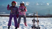 declive : Little girls in outwear and masks with helmet sitting on wood fence with skis near against mountains Stock Footage