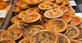 tarte : Close up panning view of a display of different variety quiches, french pies. Selective focus Stock Footage