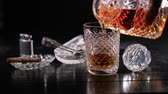 tumblers : Slow motion: Pouring whiskey from a crystal decanter into a tumbler Stock Footage