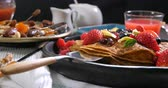 panquecas : Dolly view of a breakfast of pancakes with berries and dry fruits, defocused background