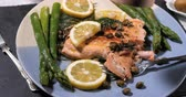 capers : Sprinkling black pepper over a delicious roasted organic salmon with capers and dill