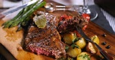 thyme : Dolly close up push in view of a delicious sirloin steak with asparagus, potatoes and roasted tomatoes