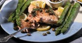 Dolly panning view of a delicious roasted organic salmon with capers and dill