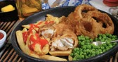 fish and chips : Squeezing tartar sauce over an English fish and chips with garden peas and ring onions