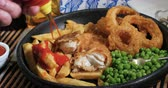 уксус : Squeezing tomato ketchup over an English fish and chips with garden peas and ring onions