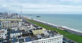 Aerial dolly view of the town of Brighton and Hove towards the beach and the two piers