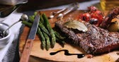 Dolly view of a delicious sirloin steak with asparagus, potatoes and roasted tomatoes
