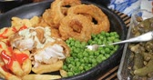 Dolly push in zoom out view of an English fish and chips with garden peas, ring onions and mushy peas