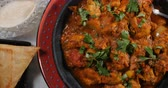 sag : Dolly top down view of a delicious chicken tikka masala with Indian spices