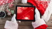refreshment time : Digital composite of Santa using tablet with Christmas snowflakes