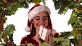 падуб : Digital composite of Santa woman opening gift with holly border Стоковые видеозаписи