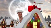 papai noel : Digital composite of Santa clause on a roof of a decorated house in winter scenery combined with falling snow