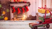 vime : Digital composite of Model car with presents on its roof and blurred background of a living room decorated for christmas combined with falling snow Stock Footage