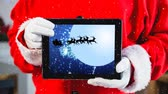 cláusula : Digital composite of Video composition with snow over torso of  santa holding tablet