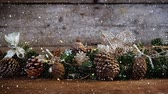 decorativo : Digital composite of Video composition with falling snow over desk with many pine cones Vídeos