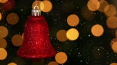 dijital oluşturulan görüntü : Digital composite of Video composition with falling snow over blurry video of Christmas tree lights and red bell