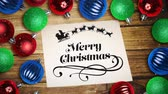 csecsebecse : Digital composite of Falling snow and Merry Christmas text note and bauble decorations on wood
