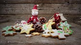 szyszka : Digital composite of Video composition with falling snow over desk with ginger cookies and santa doll
