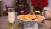 indulgence concept : Digital composite of Falling snow with Christmas treat for Santa with cookies and milk