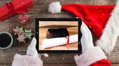 tied up : Digital composite of Video composition with snow over  of top view of  santa holding tablet