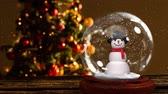 sněhulák : Cute Christmas animation of snowman against Christmas tree. Snow falling over snow globe 4k