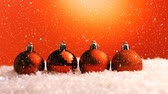 csecsebecse : Christmas animation of glittery orange Christmas baubles placed in a row in snow. Snow falling against the orange background 4k