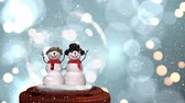 sněhulák : Cute Christmas animation of snowman couple in snow globe. Snow is falling over glittering bokeh background 4k Dostupné videozáznamy
