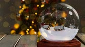snow globe : Christmas animation of snow houses in snow globe on wooden table. Snow is falling against Christmas tree bokeh Stock Footage