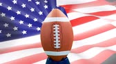 идентичность : Digital animation of rugby ball against the American Flag. American flag swaying in background 4K Стоковые видеозаписи