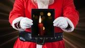 padesátých let : Digital animation of santaclaus holding digital tablet, Candle glowing on the screen 4k