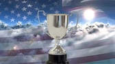 インセンティブ : Digital composite of American flag blowing in the wind with clouds background and silver trophy