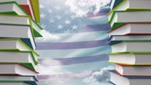 eğitim : Towers of school books against american flag blowing in the wind background Stok Video