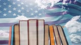 čest : Lined up books against animated american flag blowing in the sunny sky background
