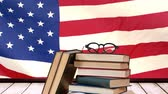 teach : Staple of books with glasses against animated american flag with sky background