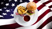 čest : Composite of food plate with burger and fries against animated american flag background