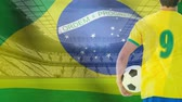 브라질 : Brazil Flag blowing in the wind at stadium with football player holding football