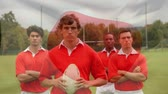 oval shape : Digital composite diverse rugby players standing on field against Japanese flag background