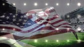 plunge : Digital composite of american football player jumping and catching ball in football stadium with american flag floating against bright spotlight background