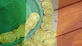 trojlístek : Digital composite of gold coins and green hat placed on wooden table with Irish flag waving on the foreground for St Patricks Day
