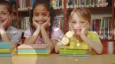 literatura : Front view of three multi ethnic schoolgirls leaning on a table and looking at the camera with books in front of them in a library against bookshelf in background