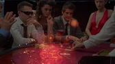 gaming chips : Digital composite of Caucasians poker players sitting around a poker table with animation of light effects in the foreground. The croupier distributing cards