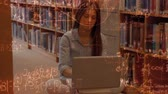 educacional : Digital composite of Caucasian woman taping in her laptop sitting in the library surrounded by animation of mathematics symbols