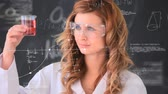 comparação : Digital composite of Caucasian woman scientist conducting experiments against an animation of scientific symbols. She is smiling and looking at camera